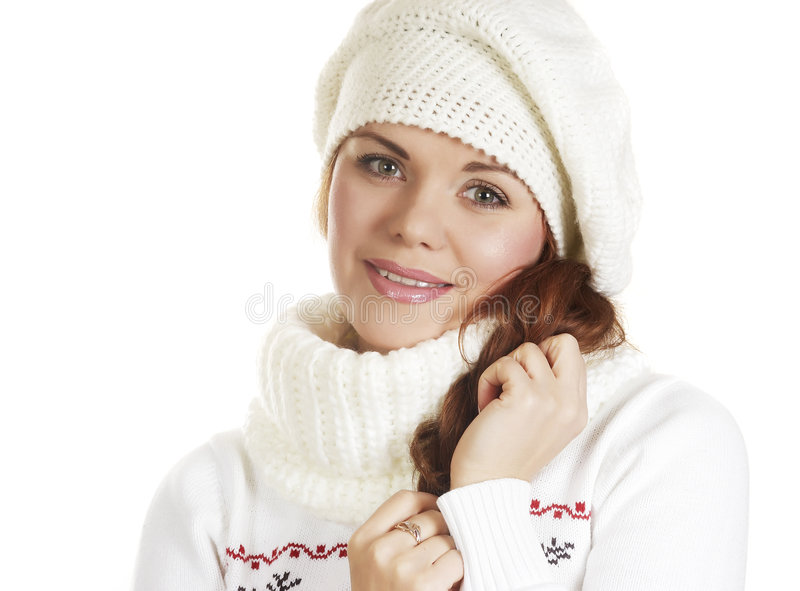Beautiful girl in winter clothes holds a hair. The beautiful young woman in a white winter sweater stock images