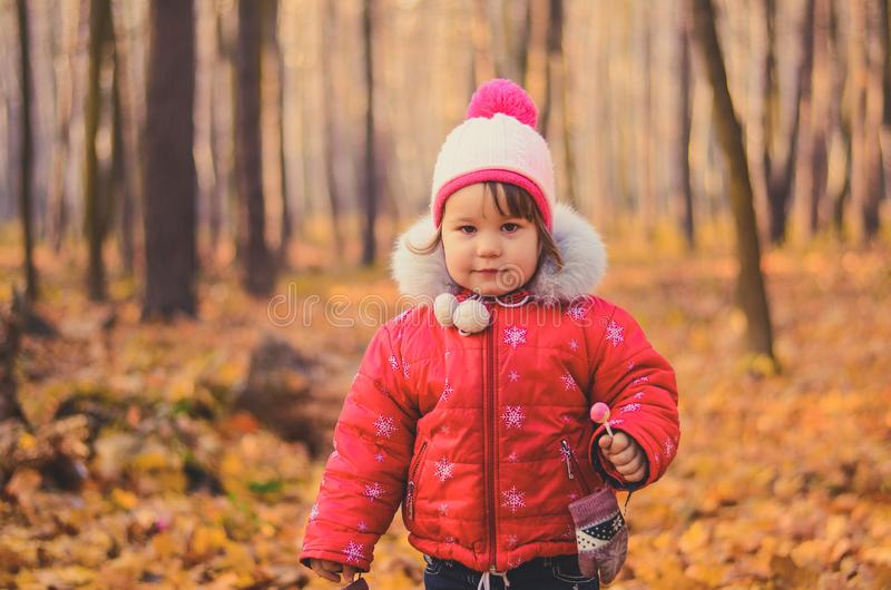 Beautiful girl in winter clothes with lollipop in the autumn park stock photography