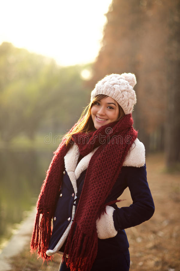 Beautiful girl in winter clothes smiling with sunset royalty free stock image