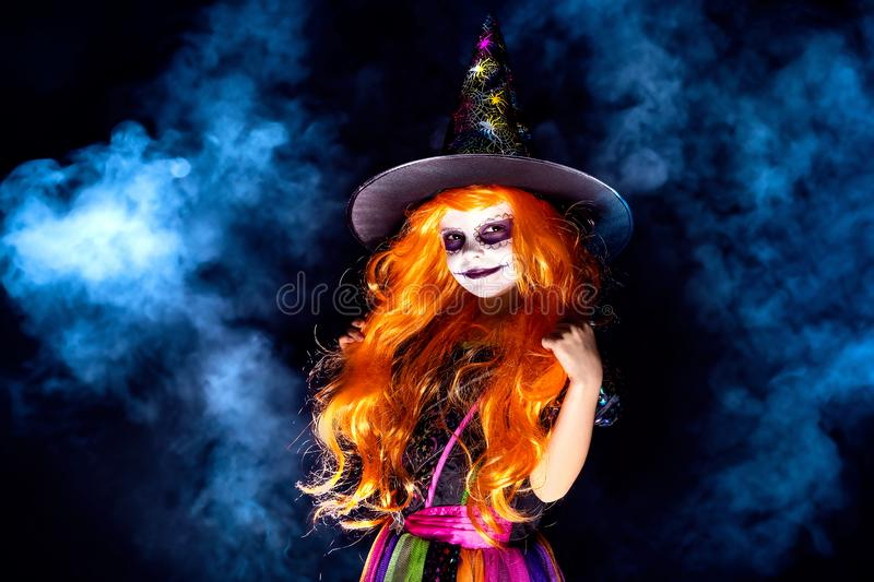 Beautiful girl in a witch costume on a dark background in smoke. stock photography