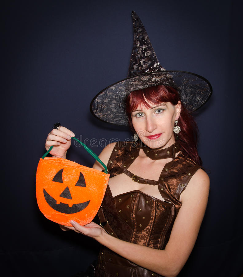 Beautiful girl in the witch dress with crazy pumpkin bag royalty free stock photo