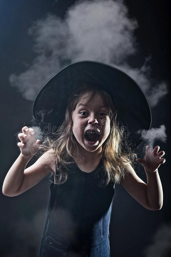 Beautiful girl in a witch hat on a dark background in smoke. stock photo