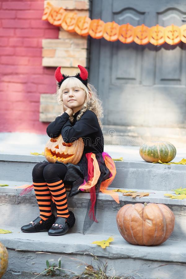 Little girl in witch costume celebrate Halloween outdoor and have fun. Beautiful girl witch. little girl in witch costume celebrate Halloween outdoor and have royalty free stock images