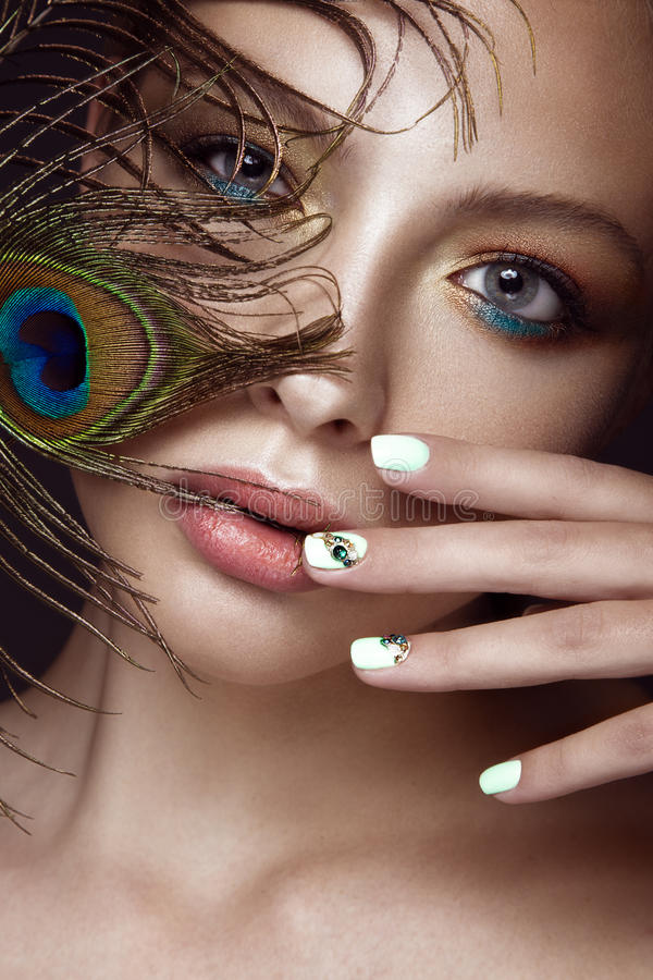 Free Beautiful Girl With Bright Makeup, Manicure Design And Peacock Feather On Her Face. Art Nails. Royalty Free Stock Photo - 66714475