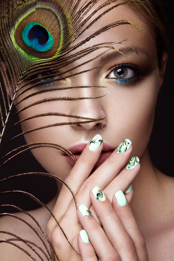 Free Beautiful Girl With Bright Makeup, Manicure Design And Peacock Feather On Her Face. Art Nails. Stock Photo - 66771100