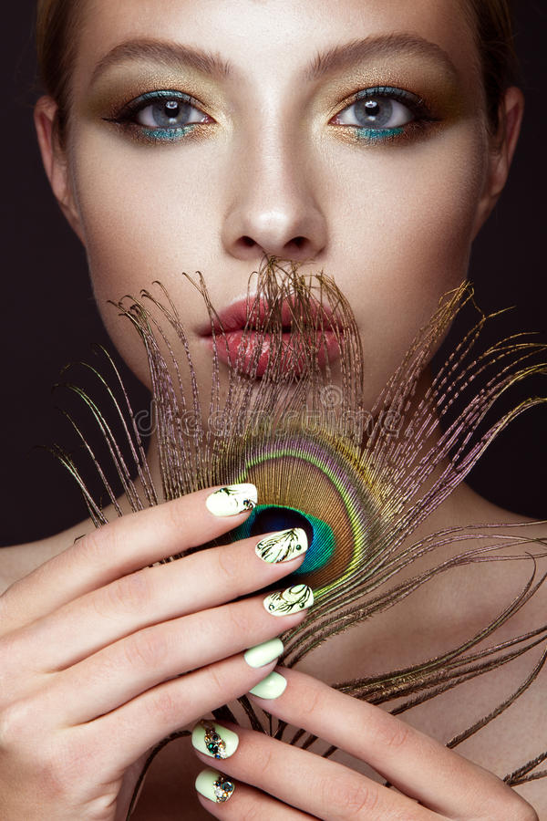 Free Beautiful Girl With Bright Makeup, Manicure Design And Peacock Feather On Her Face. Art Nails. Stock Photo - 66775460