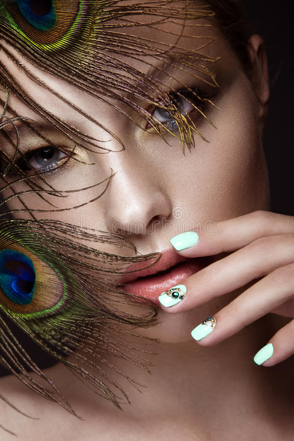 Free Beautiful Girl With Bright Makeup, Manicure Design And Peacock Feather On Her Face. Art Nails. Stock Image - 72600221