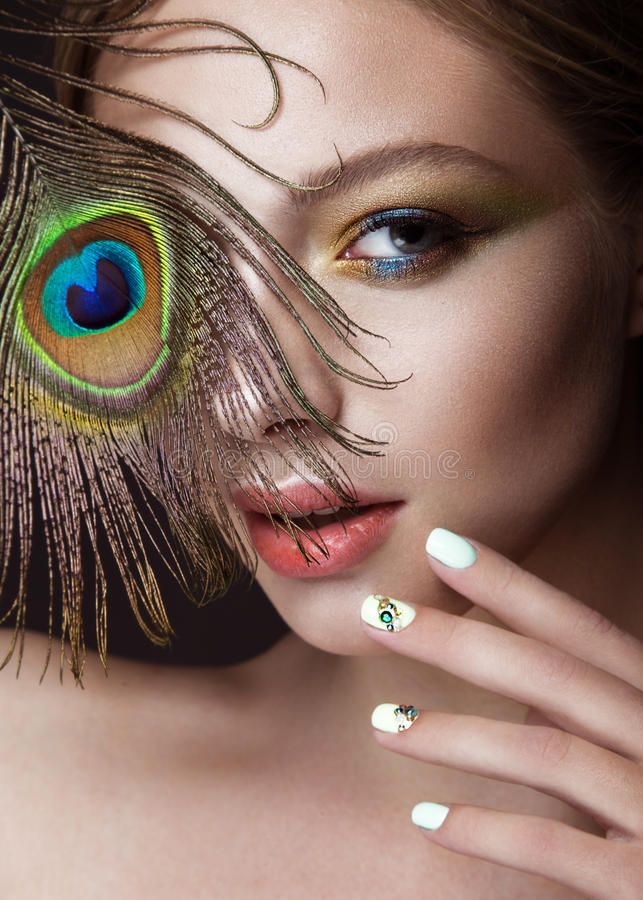 Free Beautiful Girl With Bright Makeup, Manicure Design And Peacock Feather On Her Face. Art Nails. Stock Photos - 72601463