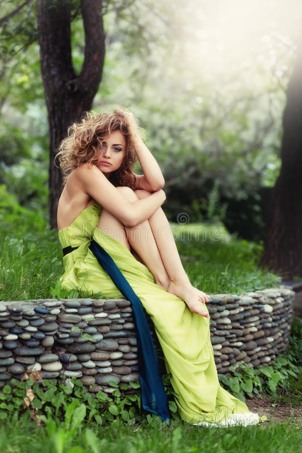 Free Beautiful Girl With Curly Hair Sitting On The Grass. Royalty Free Stock Photos - 90087558