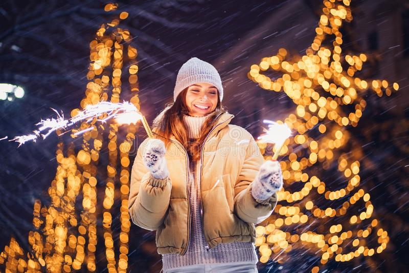 Beautiful girl or woman holding sparkles and have fun in the open air royalty free stock image