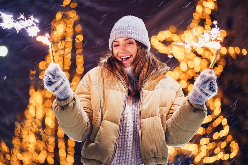 Beautiful girl or woman holding sparkles and have fun in the open air stock photography