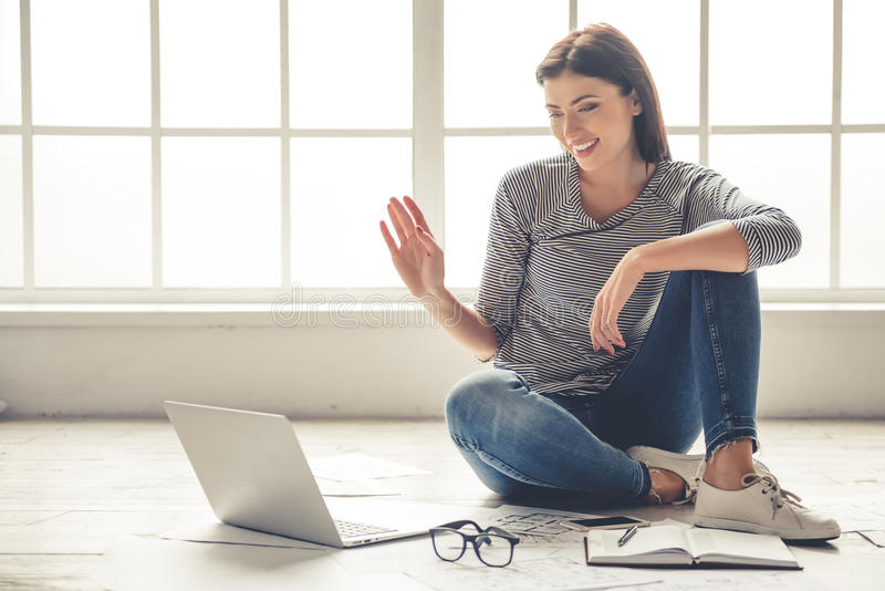 Beautiful girl working at home. Beautiful business lady in casual clothes is using a laptop, waving and smiling while sitting on the floor at home and working stock photos