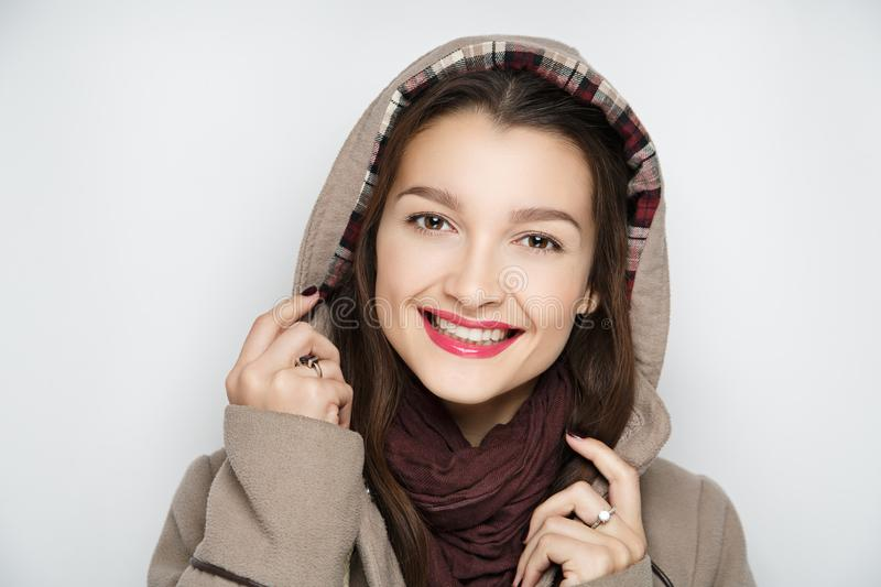 Girl in an autumn raincoat. Beautiful girl is wrapped up in a raincoat. Autumn fashion look. Volume scarf tied around neck. Girl holds big hood in her fingers stock photography