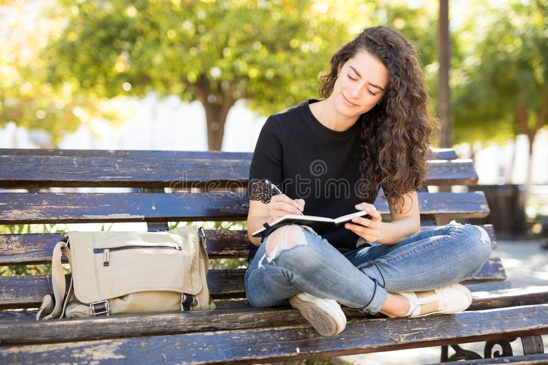 Beautiful girl writing in a journal at park stock images