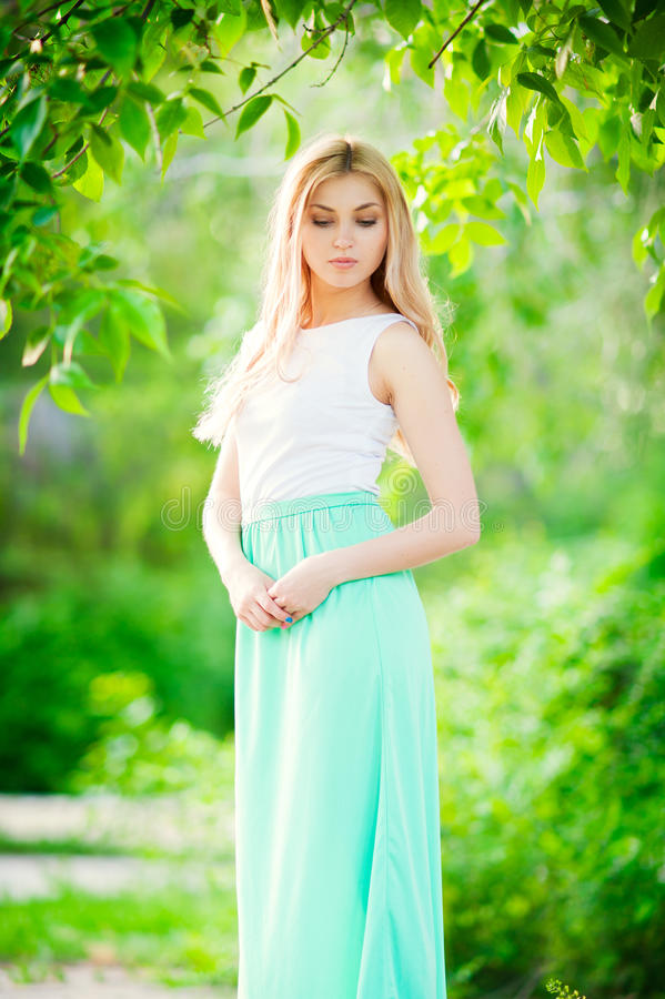 Beautiful girl. Beautiful Young happy Woman Outdoors in a long dress looking down royalty free stock photos