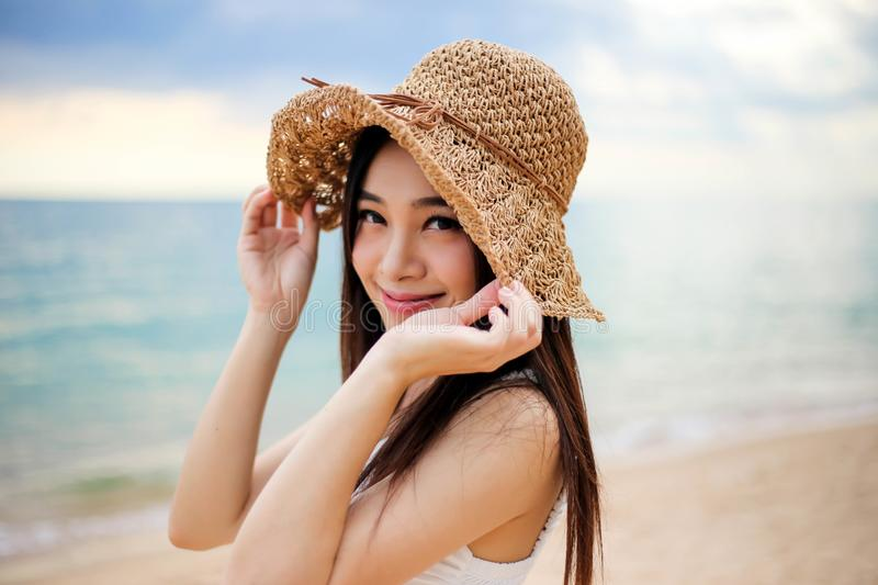 Beautiful girl young woman asia in a  hat smiling on the beach at sunset,enjoy summer vacation on the beach royalty free stock photos