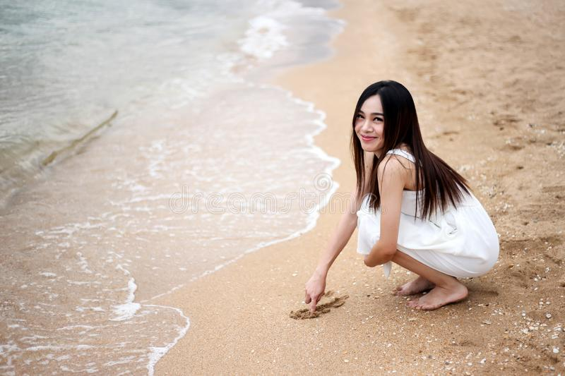 Beautiful girl young woman asia writing in the sand on beach ,on summer holiday vacation enjoying the beach stock photo