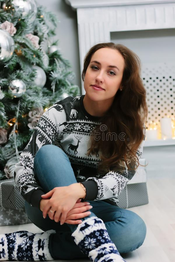 Beautiful girl or young woman sitting near the christmas tree royalty free stock photography