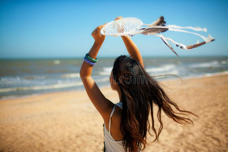 Beautiful girl young woman in white dress on the beach with dream Catcher, in Boho style,. Beautiful girl young woman in white dress on the beach with dream stock photography