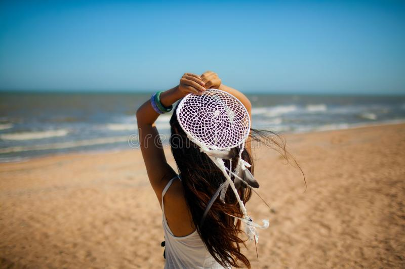 Beautiful girl young woman in white dress on the beach with dream Catcher, in Boho style,. Beautiful girl young woman in white dress on the beach with dream royalty free stock photos