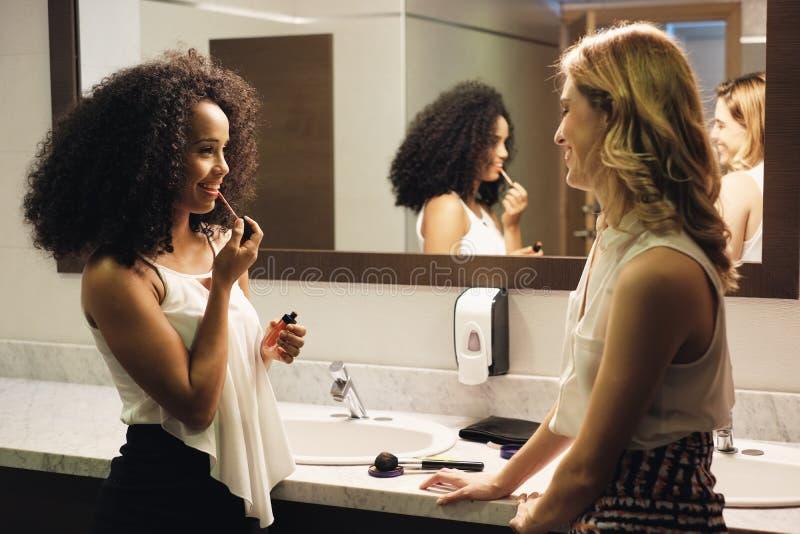 Beautiful Girls As Happy Friends Talking For Gossip In Restroom royalty free stock photo