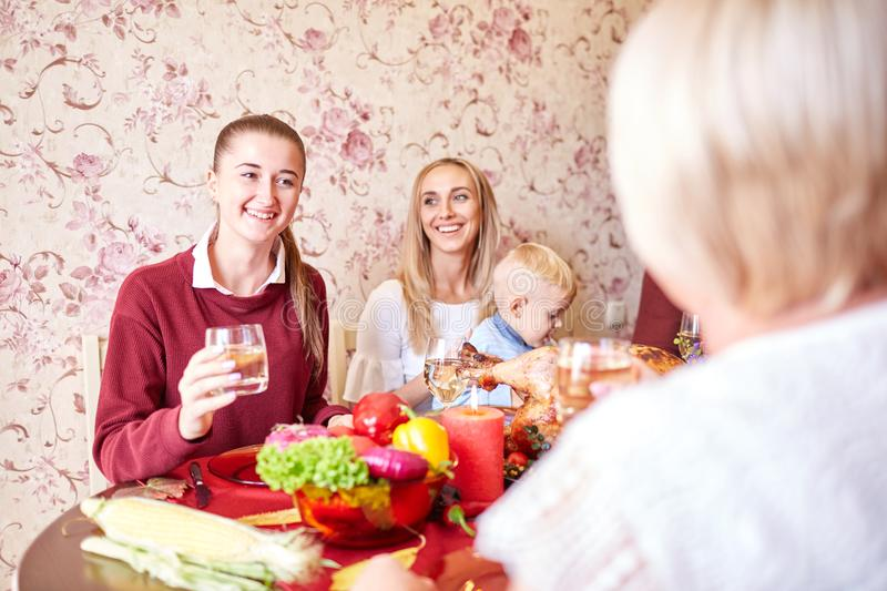 Beautiful girls and baby boy sitting at the festive table on a home background. Family smiling at Christmas dinner. Gorgeous, happy sisters and a baby son royalty free stock image
