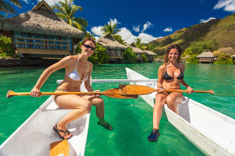 Beautiful girls in bikini relaxing on a canoe at the tropical re. Sort beach stock image