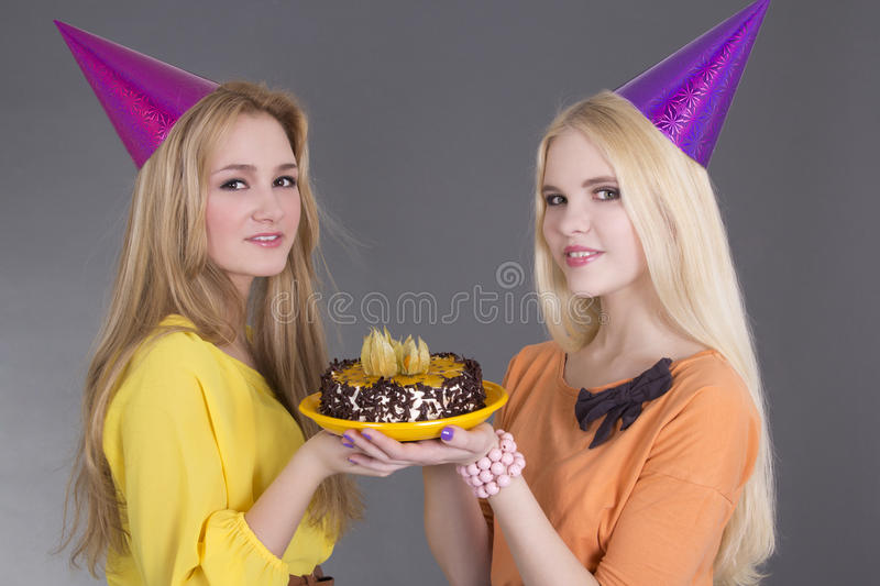 Beautiful girls with birthday cake. Over grey stock image