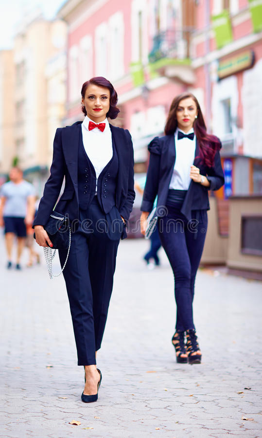 Beautiful girls in black suits walking the street royalty free stock photo
