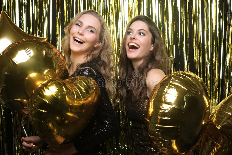 Beautiful girls celebrating New Year. Gorgeous smiling young women enjoying party celebration, having fun together royalty free stock images