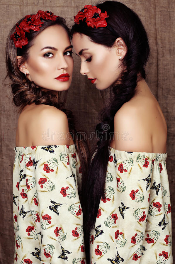 Beautiful girls with dark hair in dresses with prints of red poppies stock photo