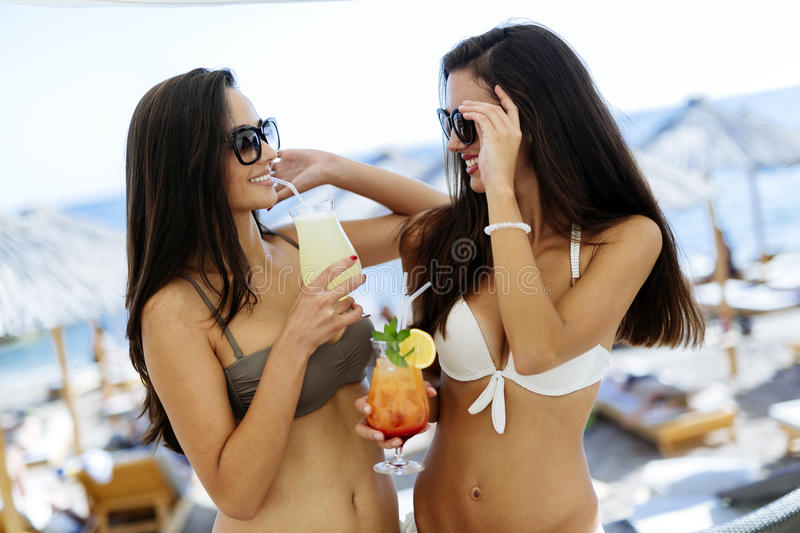 Beautiful girls drinking cocktails on beach royalty free stock images
