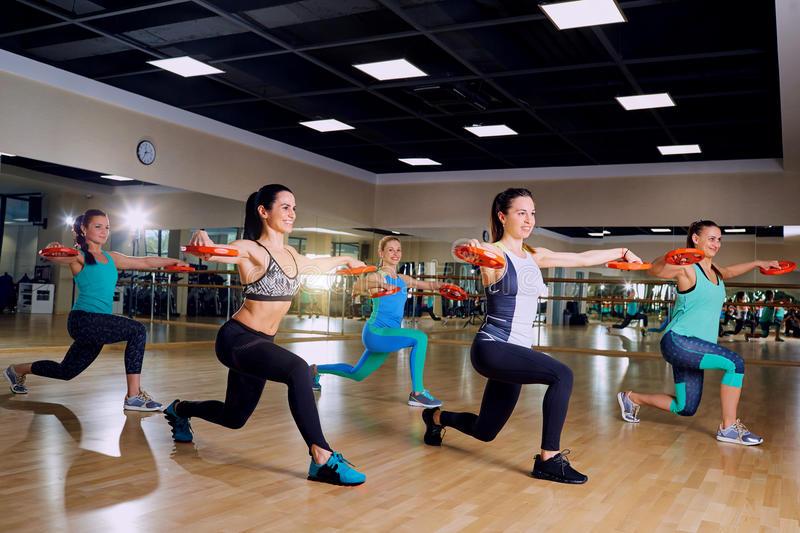 Beautiful girls are engaged in group training in the gym royalty free stock images