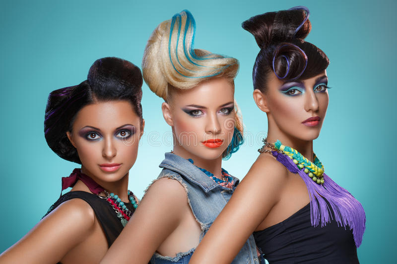Beautiful girls with fancy hairstyles and vivid makeup. Three beautiful young women with fancy hairstyles and bright makeup. Beauty shot over blue background stock image