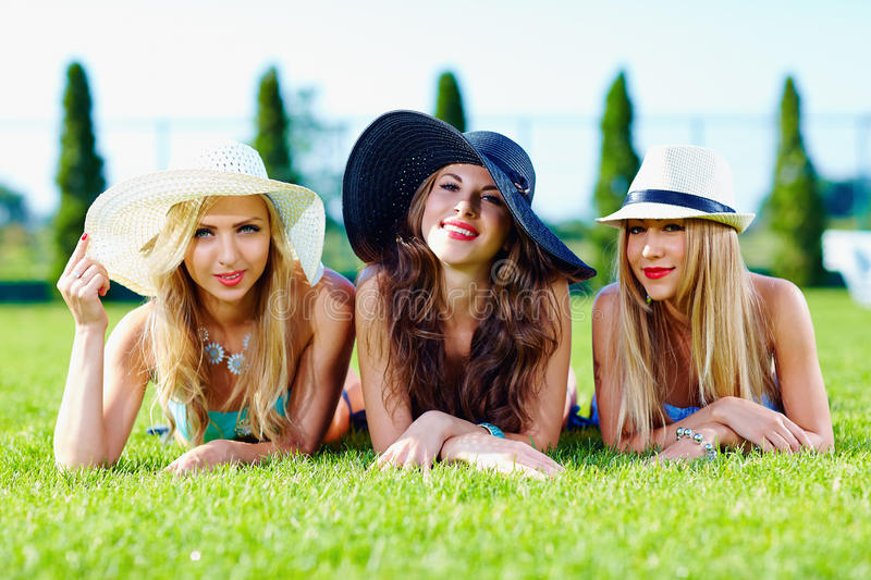 Beautiful girls in hats relaxing on summer meadow stock photography