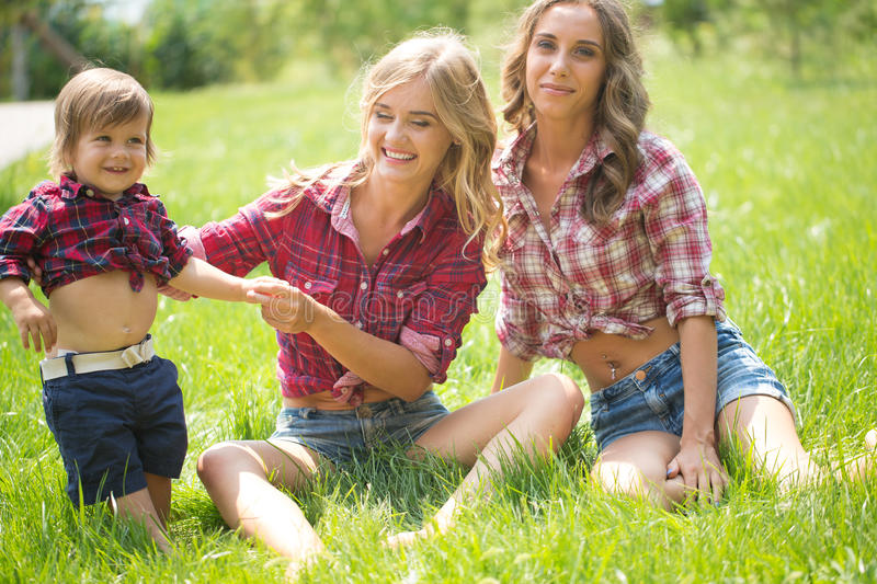 Beautiful girls with little boy on the grass royalty free stock images