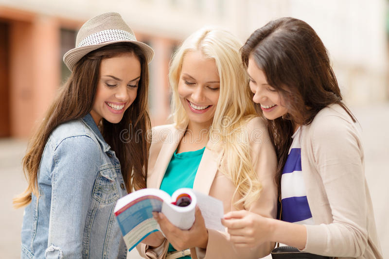 Beautiful girls looking into tourist book in city