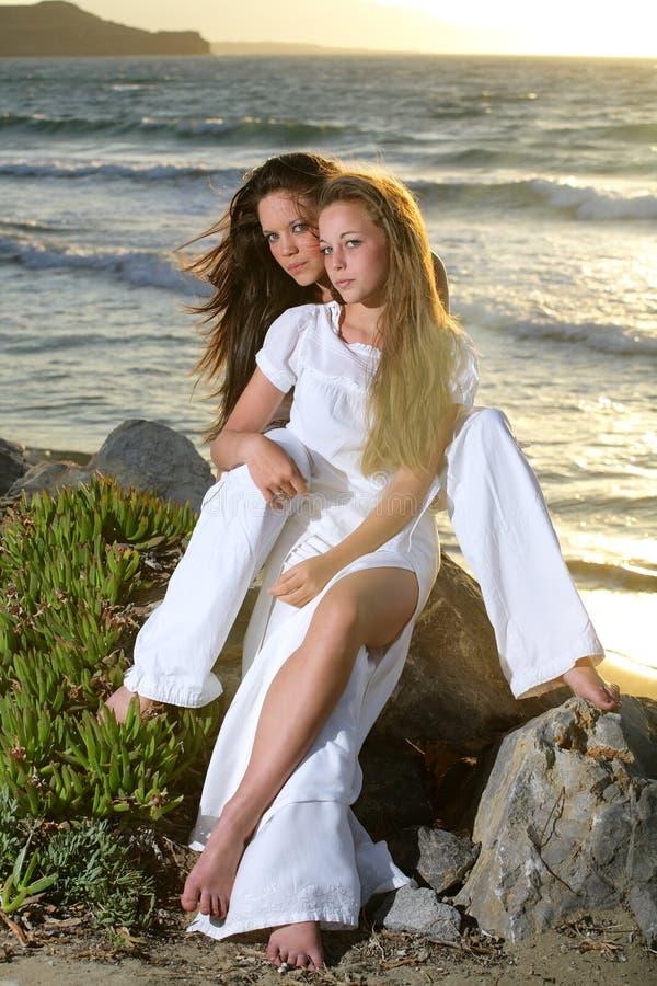 Beautiful girls over sunset background. Beautiful teenage girls over sea and sunset background royalty free stock photography