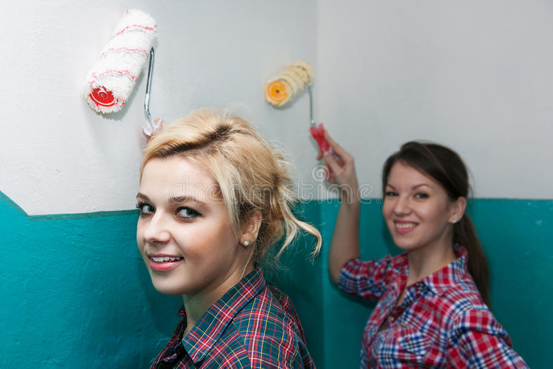 Beautiful girls paint the walls stock photography
