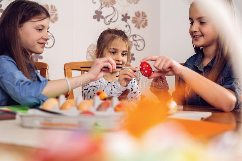 Beautiful girls painting eggs for Easter holiday stock photos