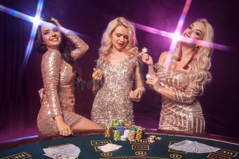 Beautiful girls with a perfect hairstyles and bright make-up are posing standing at a gambling table. Casino, poker. stock photos