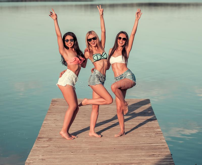 Girls on the sea. Beautiful girls are posing at camera and smiling while standing on pier at the sea stock images