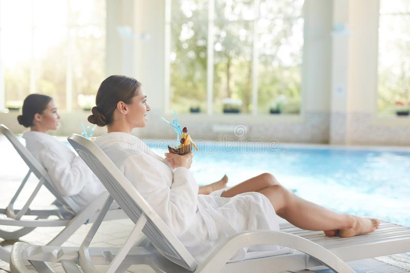 Beautiful Girls Relaxing by Pool royalty free stock image