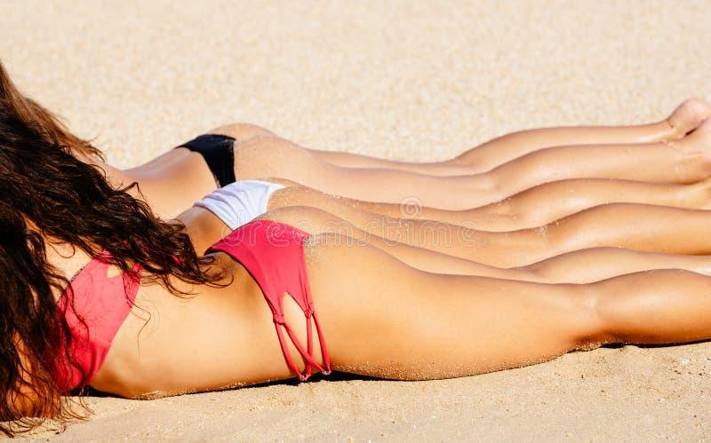 Beautiful Girls in Bikinis Sunbathing. On the Beach. Summer fun lifestyle royalty free stock photo