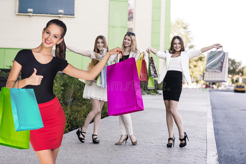 Beautiful girls with shopping bags near mall. royalty free stock photo