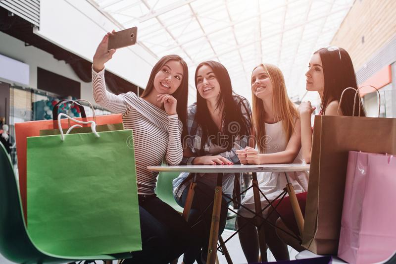 Beautiful girls are sitting at table and talking selfie. Asian girl is holding camera and taking picture of it. There stock photos