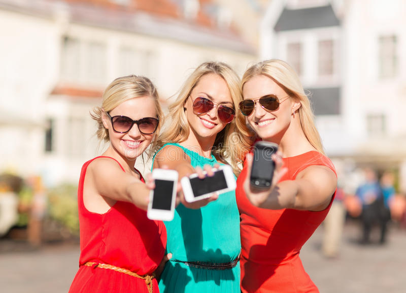 Beautiful girls with smartphones in the city stock image