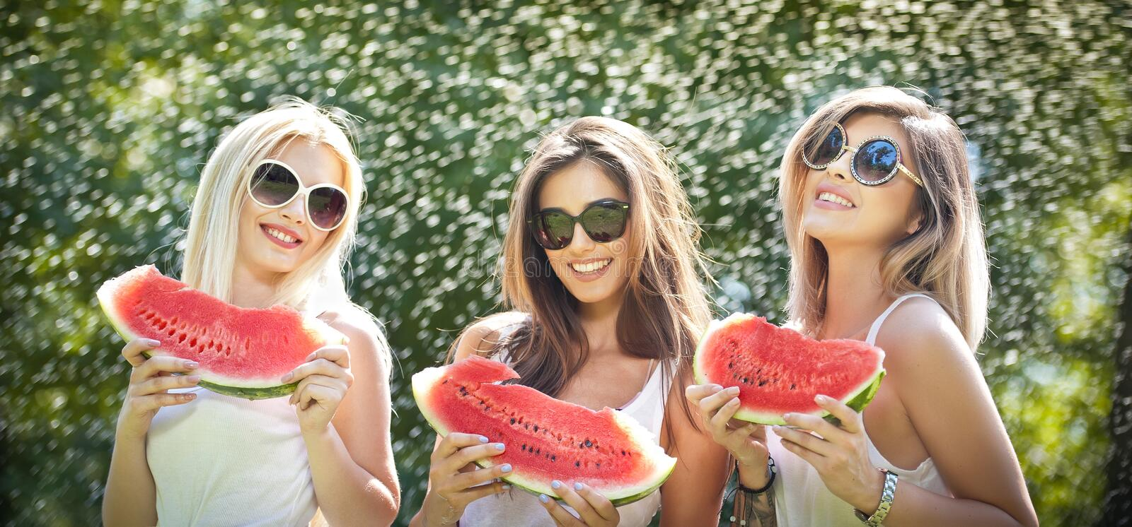 Beautiful girls with sunglasses eating fresh watermelon laughing. Happy young women holding watermelon slices outdoors stock photography