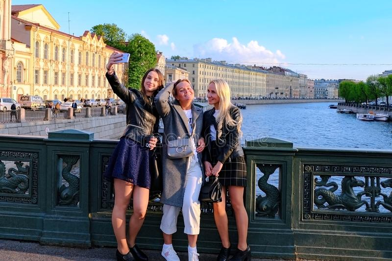 Beautiful girls take selfies on the bridge over the river. Summer tourist season. Saint-Petersburg. Russia. 06.24.2019 royalty free stock image
