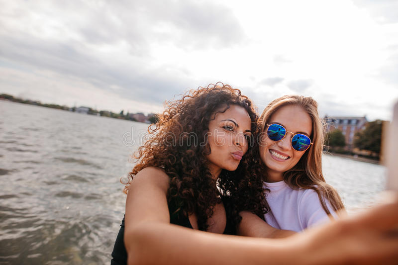 Beautiful girls taking selfie with mobile phone by the lake. stock photo